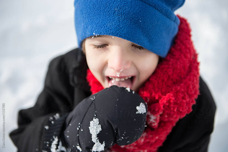 Boy plays outside in the snow by Cara Dolan for Stocksy United