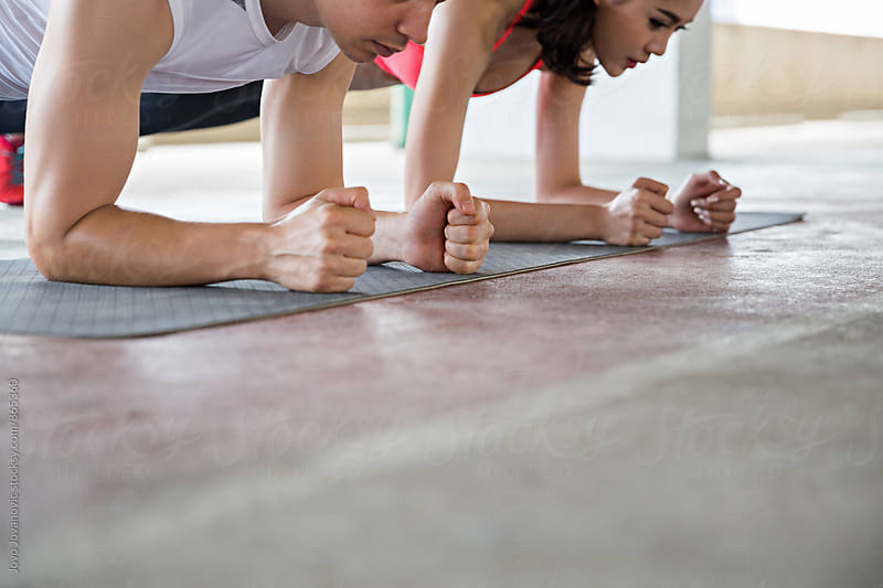 Closeup of two young people in plank position on gym mats  by Jovo Jovanovic for Stocksy United