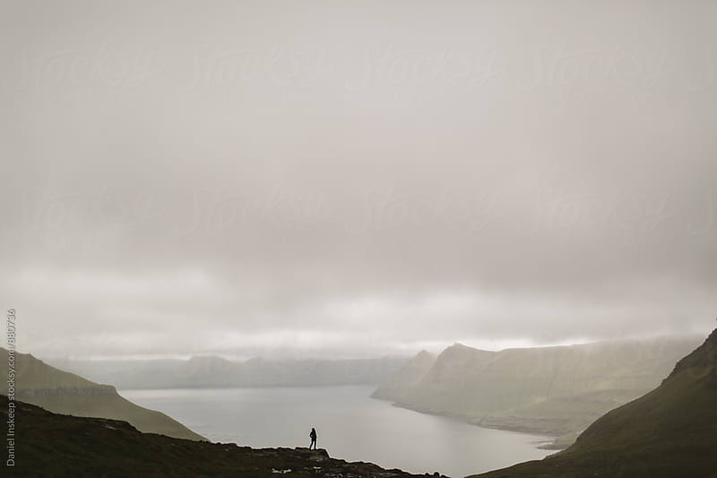 A Woman Looking Out at a Foggy Inlet by Daniel Inskeep for Stocksy United