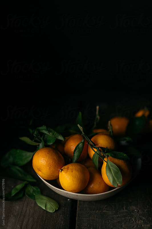 portrait of oranges on wood kitchen table by Levi Tijerina for Stocksy United