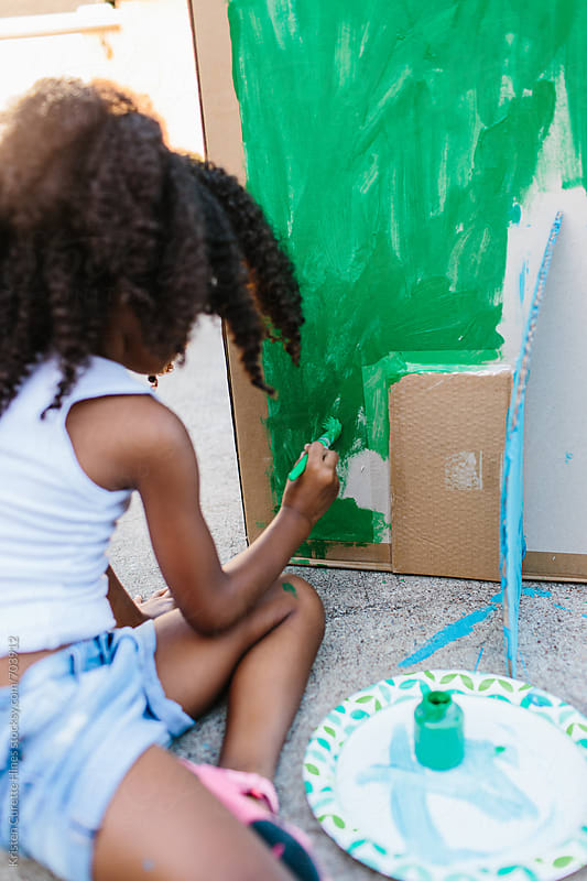 A child painting a card board box green by Kristen Curette Hines for Stocksy United