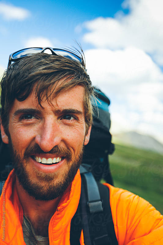 Man hiking and smiling by Matthew Spaulding for Stocksy United