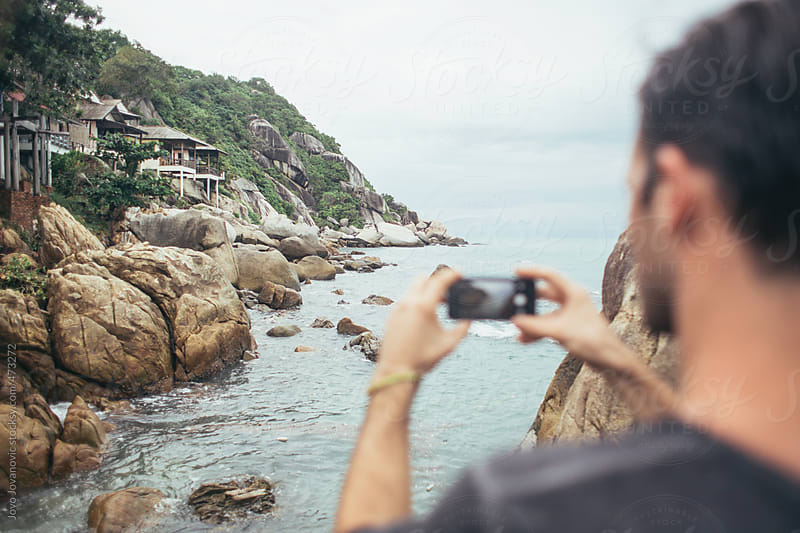 Young man taking a photo with his phone of buildings along a rocky coastline by the water by Jovo Jovanovic for Stocksy United