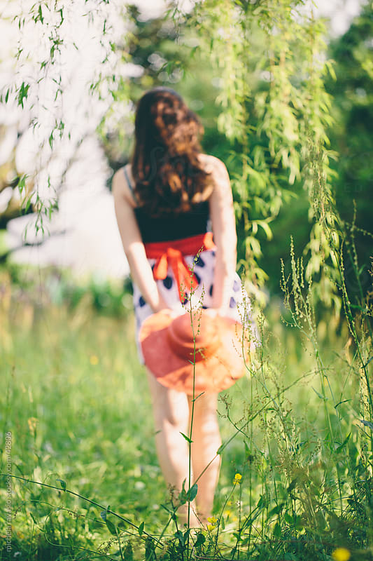 Young woman walking in a meadow  by michela ravasio for Stocksy United