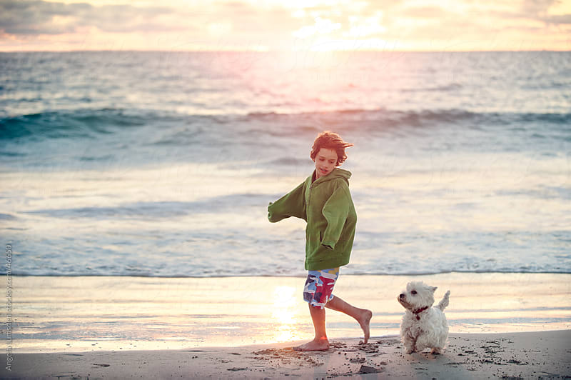 Boy running with his dog at beach at sunset by Angela Lumsden for Stocksy United