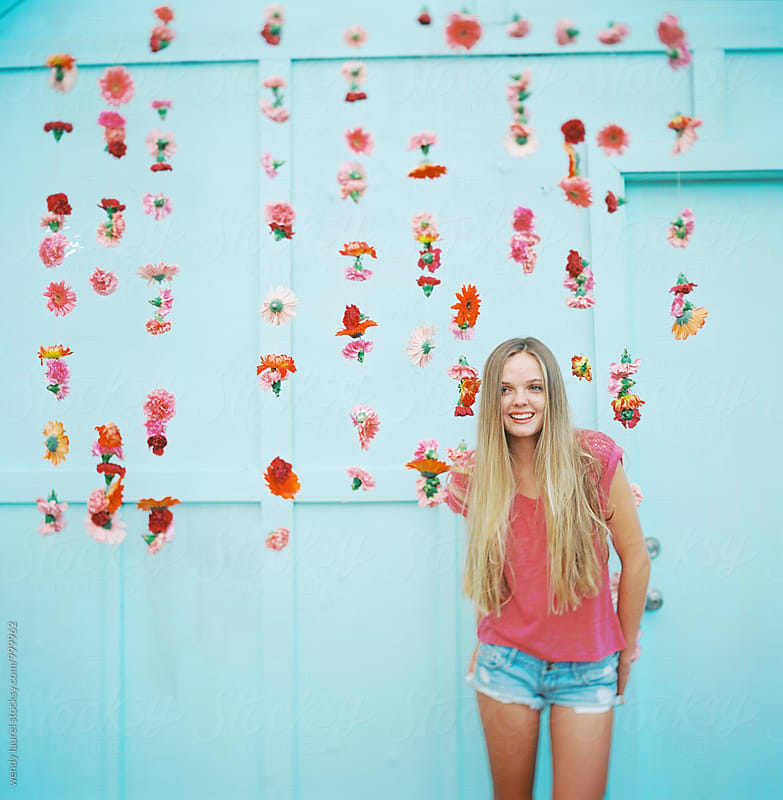 blonde girl laughing in front of blue wall and hanging pink flowers by wendy laurel for Stocksy United