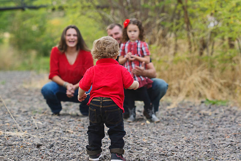 toddler walks toward his family by Tana Teel for Stocksy United