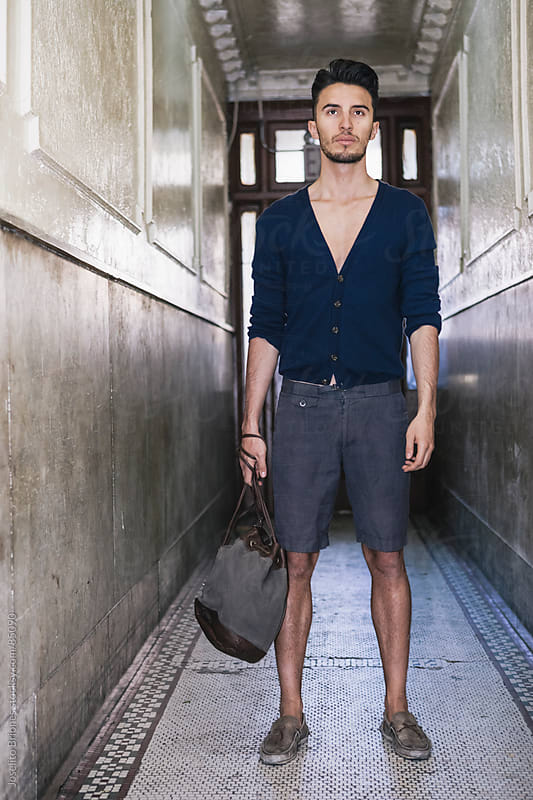Young Man in Cardigan and Shorts Standing in Hallway by Joselito Briones for Stocksy United