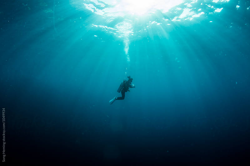 A scuba diver diving under sunlight by Song Heming for Stocksy United