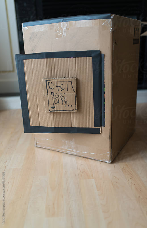 cardboard box decorated with numbers printed by child by Tara Romasanta for Stocksy United
