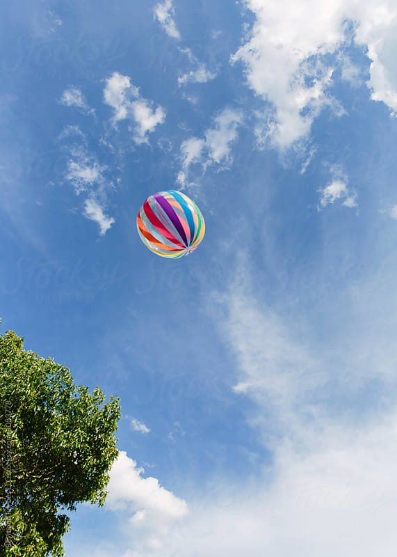Beach Ball Floating Through Summer Sky by Raymond Forbes LLC for Stocksy United