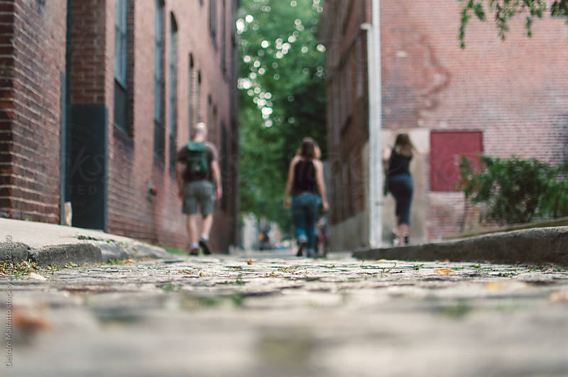 cobblestone street with family walking in distance by Deirdre Malfatto for Stocksy United
