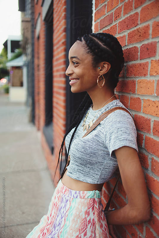 A young african american woman leaning against a brick wall by Chelsea Victoria for Stocksy United