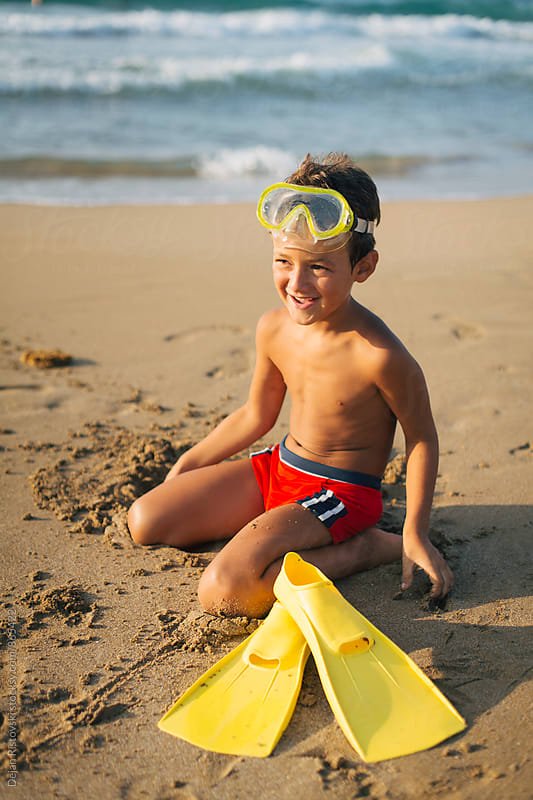 Cute boy smiling on the beach. by Dejan Ristovski for Stocksy United