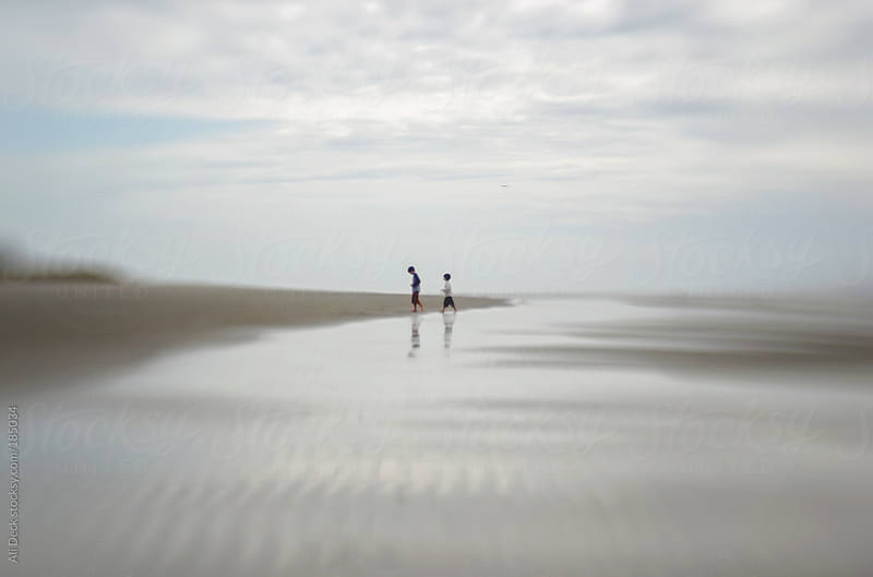 Two Boys Walk Along the Beach by Ali Deck for Stocksy United