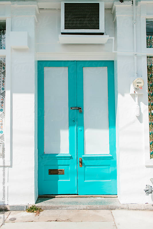 A bright cyan door on the streets of New Orleans  by Kristen Curette Hines for Stocksy United