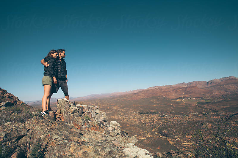 Couple hiking in the mountains enjoying the view by Micky Wiswedel for Stocksy United