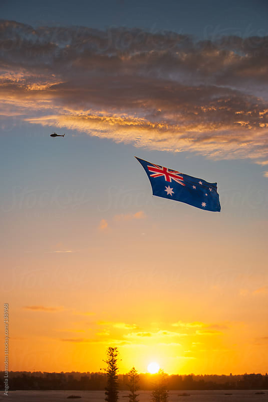 Australian flag flying over Perth at sunset on Australia Day by Angela Lumsden for Stocksy United