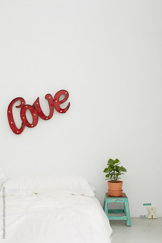 Bedroom corner for young couple with an electronic love sign by Miquel Llonch for Stocksy United