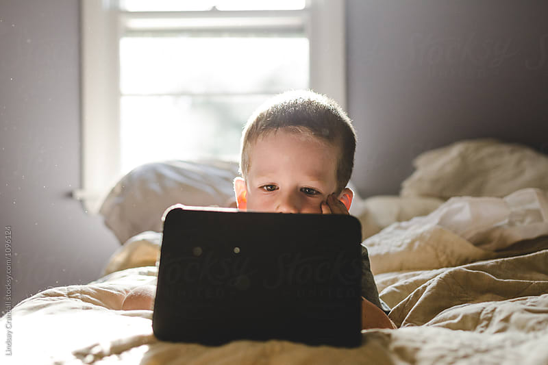 Young boy lying on bed playing with a tablet by Lindsay Crandall for Stocksy United