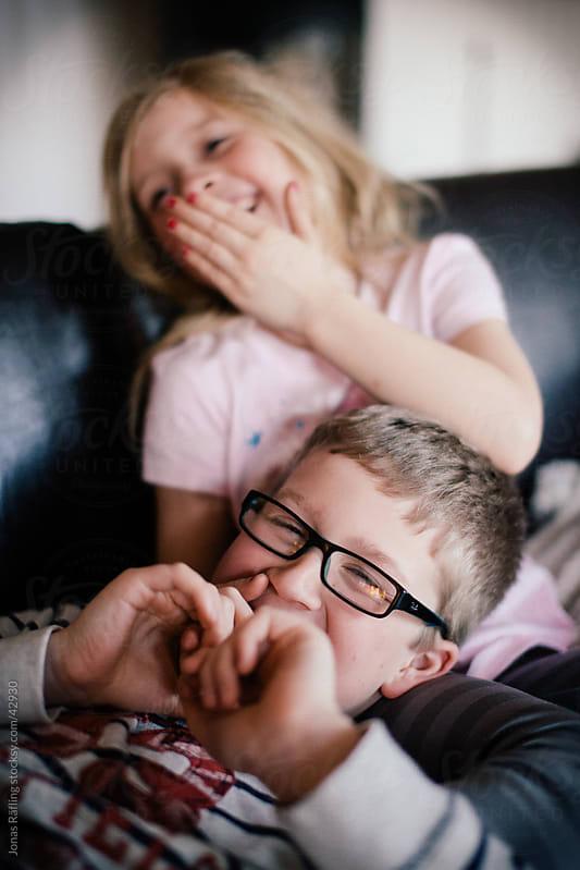 Laughing siblings by Jonas Räfling for Stocksy United