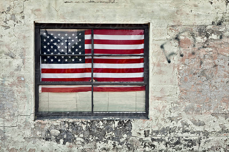 USA Flag in the window of a grungy building by David Smart for Stocksy United