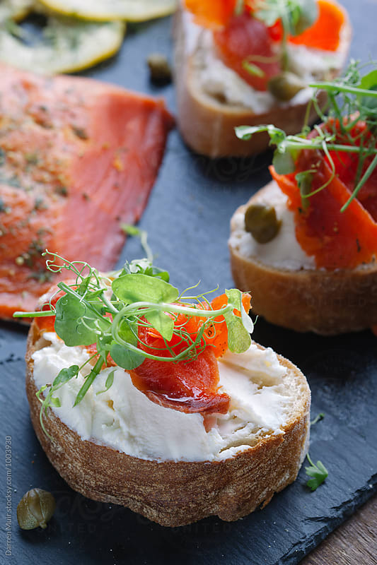 Salmon and cream cheese on sliced bread. by Darren Muir for Stocksy United