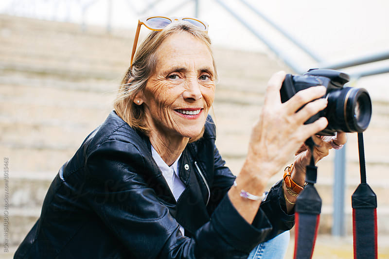Mature woman using her camera in the city. by BONNINSTUDIO for Stocksy United
