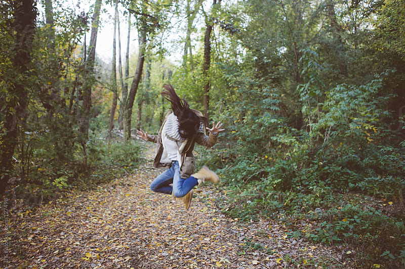 girljumping  in the woods by B & J for Stocksy United