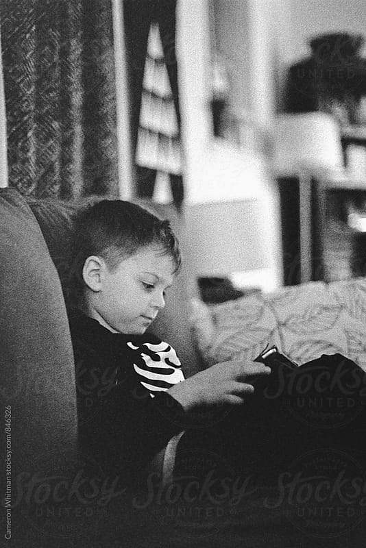 Young boy using tablet device in his PJ's by Cameron Whitman for Stocksy United