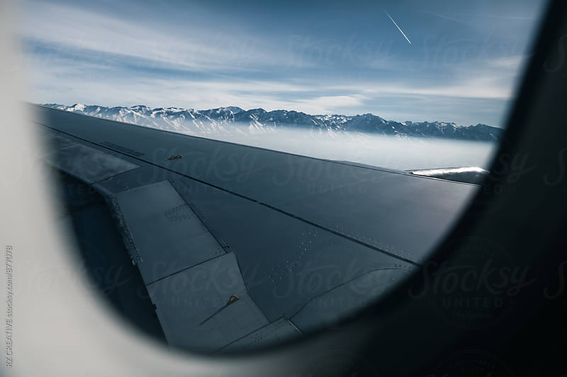 Looking out the window of a commercial airline to snowy mountains below. by Robert Zaleski for Stocksy United
