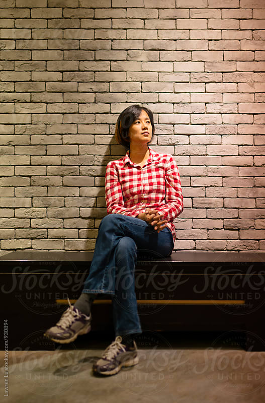 Asian woman sitting on bench while looking away by Lawren Lu for Stocksy United