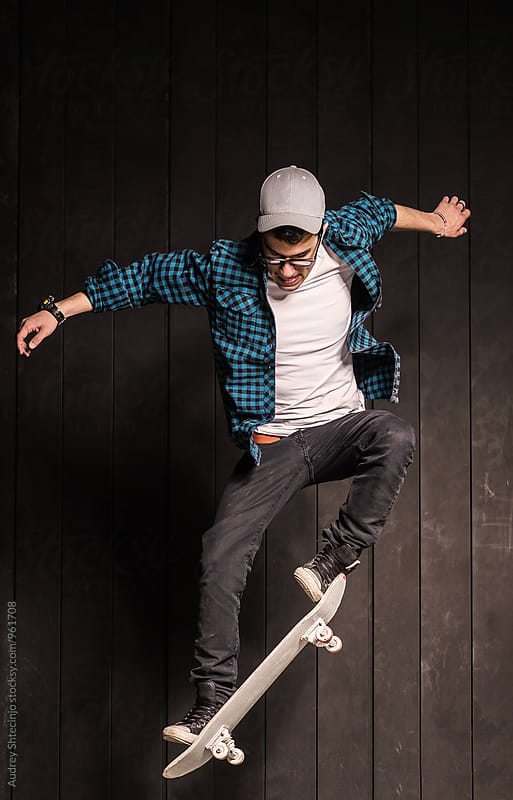 Young skater in urban outfit jumping and doing tricks. by Marko Milanovic for Stocksy United