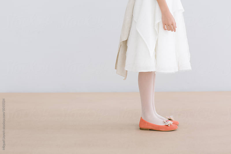 Young female with white dress and orange shoes by Miquel Llonch for Stocksy United