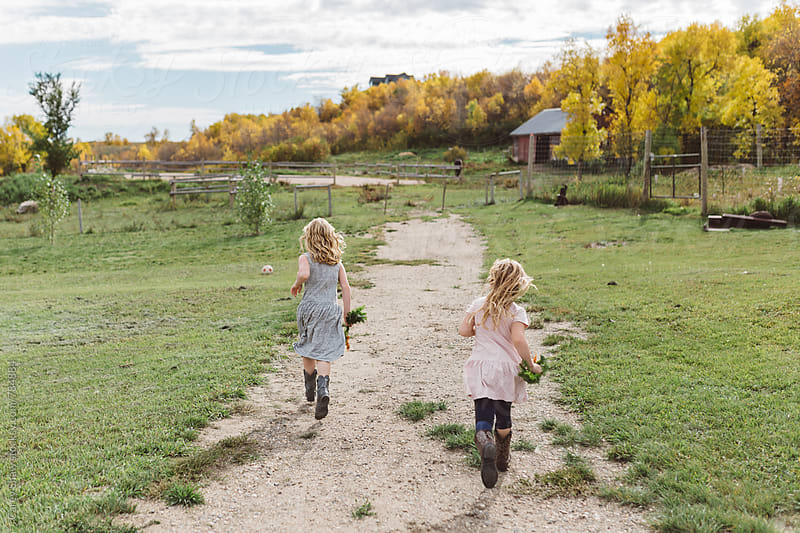 Young sisters running on farm by Carey Shaw for Stocksy United