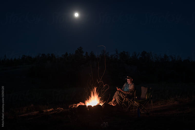Man texting by campfire by Mick Follari for Stocksy United