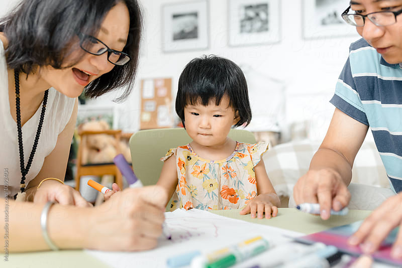 Adorable little girl drawing pictures with her parents by Maa Hoo for Stocksy United