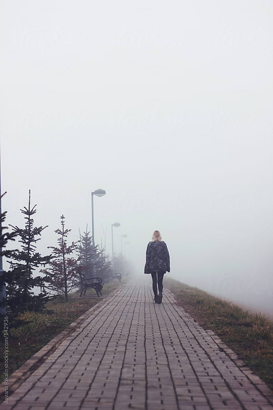 A young girl walking throug the fog by Jovana Rikalo for Stocksy United