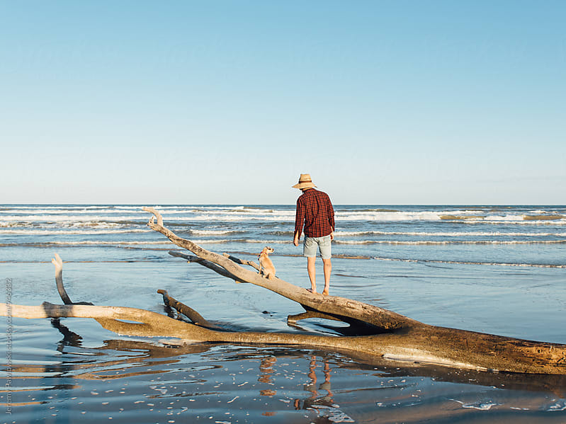 Man standing with dog on log washed up from ocean waves by Jeremy Pawlowski for Stocksy United
