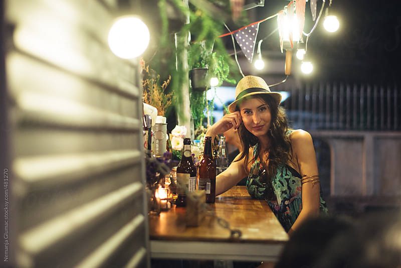 Single Young Woman Sitting at the Food Truck Counter With Beer by Nemanja Glumac for Stocksy United