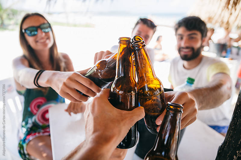 First person point of view of some friends toasting their bottles of beer during lunch in a beach bar by Alejandro Moreno de Carlos for Stocksy United