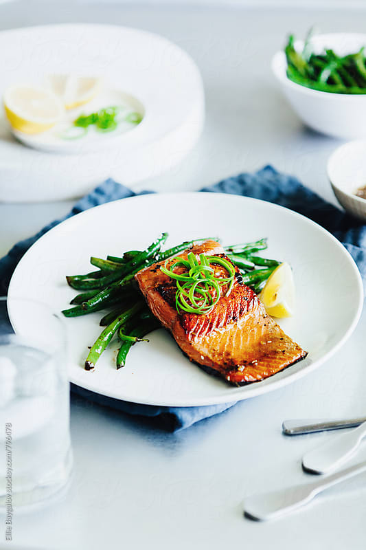 Grilled salmon on a bed of green beans  by Ellie Baygulov for Stocksy United
