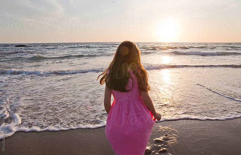 Girl in pink dress standing at ocean's edge facing sunset by Dina Giangregorio for Stocksy United