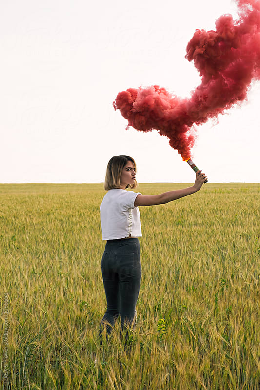 serious teen girl with red smoke bomb on meadow by T-REX & Flower for Stocksy United