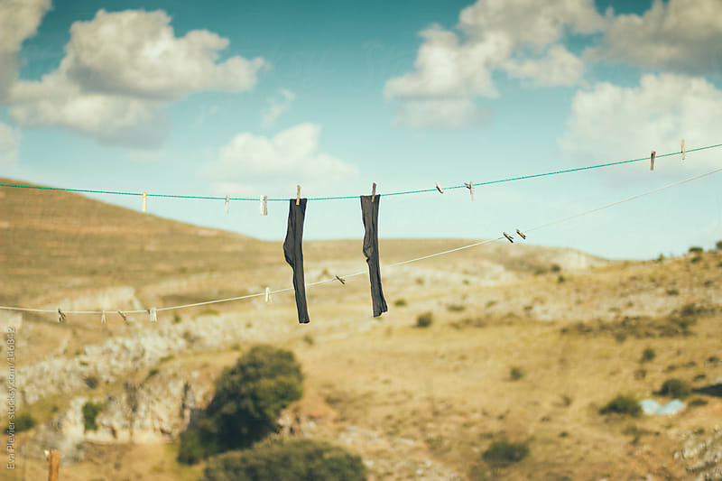 Socks hanging on a rope with pegs. by Eva Plevier for Stocksy United