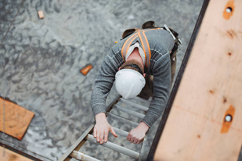 Carpenter man climbing down ladder at construction site by Rob and Julia Campbell for Stocksy United