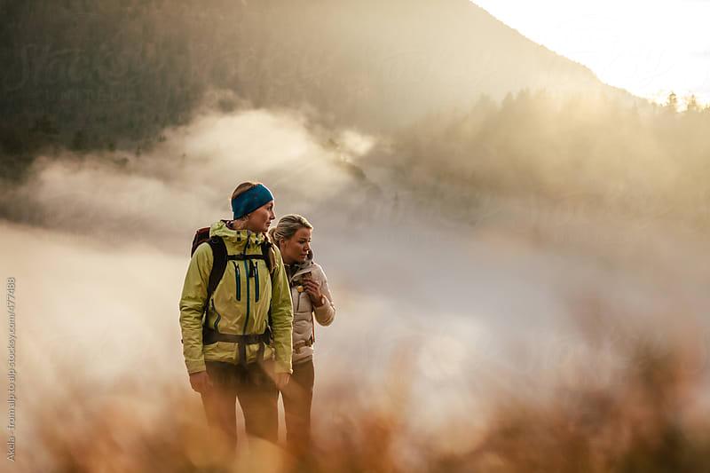 two sporty women in idyllic autumnal landscape by Leander Nardin for Stocksy United