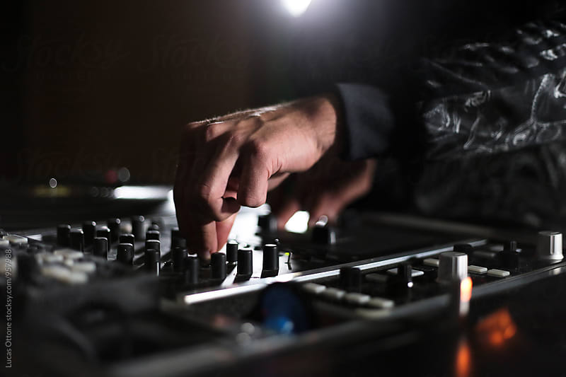 Male hands on a DJ mixing table by Lucas Ottone for Stocksy United
