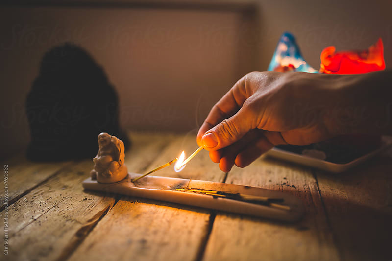 Hand lighting incense with a match by Christian Tisdale for Stocksy United