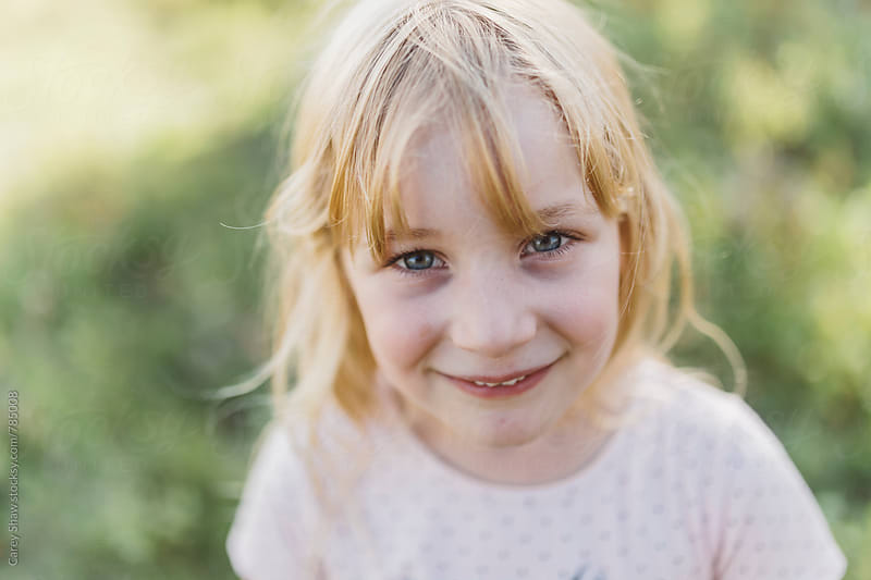 Happy young girl looking up at camera by Carey Shaw for Stocksy United